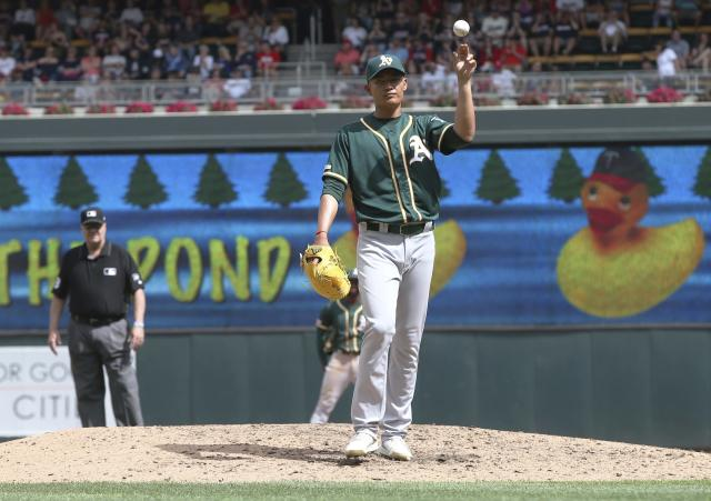 Oakland Athletics pitcher Wei-Chung Wang, of Taiwan, throws the ball to the dugout while awaiting a new one after walking Minnesota Twins' Jason Castro in the fifth inning of a baseball game Sunday, July 21, 2019, in Minneapolis. (AP Photo/Jim Mone)