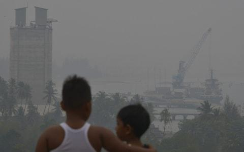 <span>Children look into the haze in Indonesia's Aceh province</span> <span>Credit: Chaideer Mahyuddin/AFP </span>