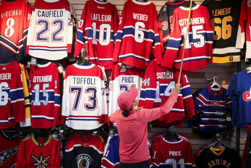 A store manager pulls down a Montreal Canadiens hockey jersey on display in his store in downtown Montreal