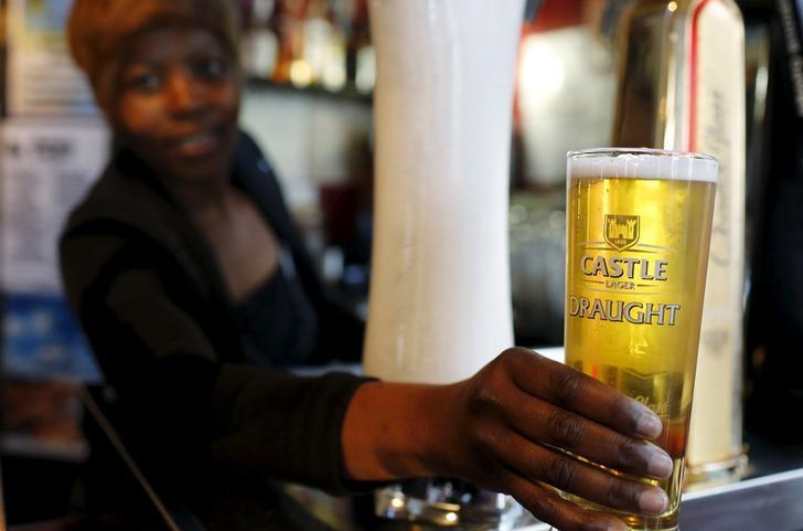 A bartender serves a beer produced by brewing company SAB Miller at a bar in Cape Town