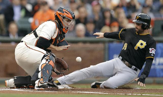 Pittsburgh Pirates' Neil Walker, right, slides to score as San Francisco Giants catcher Buster Posey waits for the ball in the first inning of a baseball game Monday, July 28, 2014, in San Francisco. Walker scored on a sacrifice fly by Pittsburgh's Gregory Polanco(AP Photo/Ben Margot)