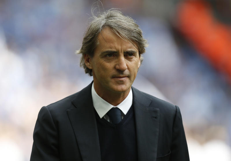 FILE - A Saturday, May 11, 2013 photo from files showing Manchester City's manager Roberto Mancini during a line up at the start of their English FA Cup final soccer match against Wigan Athletic at Wembley Stadium, London. Manchester City has fired manager Roberto Mancini after conceding the Premier League title to rival Man United and finishing the season without a trophy. The club announced the decision Monday, May 13, 2013, on its website.The Italian is departing after less than four years in charge, having ended the club's 35-year trophy drought by winning the FA Cup in 2011 and then leading the team to its first league title in 44 years the following season. (AP Photo/Jon Super, File)