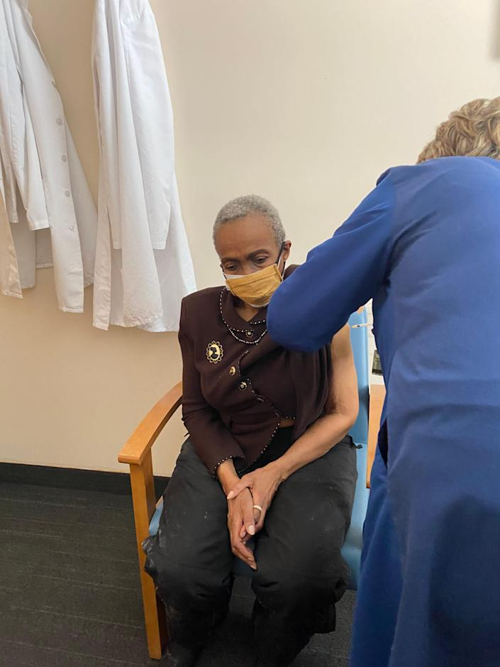 Jewelean Jackson, a patient, community health worker and former governing board chair at  Minnesota's Community-University Health Care Center, receives her first dose of the Moderna COVID-19 vaccine.