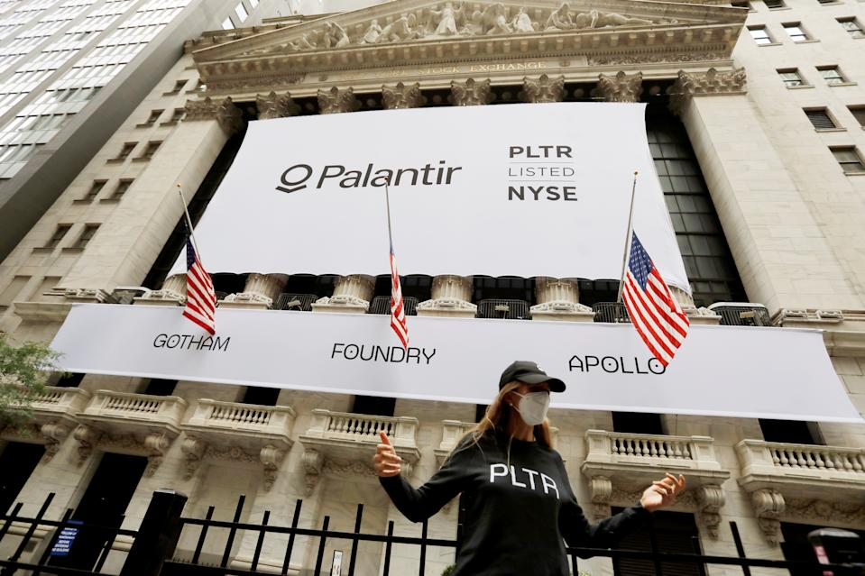A person poses in front of a banner featuring the logo of Palantir Technologies (PLTR) at the New York Stock Exchange (NYSE) on the day of their initial public offering (IPO) in Manhattan, New York City, U.S., September 30, 2020. REUTERS/Andrew Kelly