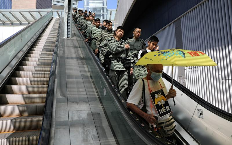 A line of police officers ride an escalator behind a protester holding an umbrella - REUTERS