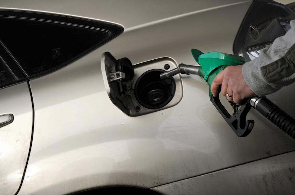 A motorist pulls the fuel pump nozzle from their car at a petrol station in Egham