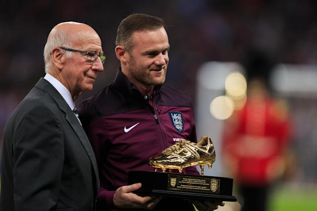Wayne Rooney receives his award for becoming England's record scorer from Sir Bobby Charlton.