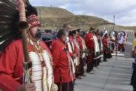 In this Wednesday, May 19, 2021, photo, members of the Black Mouth Society, a traditional group on the Fort Berthold Indian Reservation line up at an event marking the opening of the MHA Nation Interpretive Center, a cultural center and museum in New Town, North Dakota. Oil pumped from Native American lands in the U.S. increased almost tenfold since 2009 to more than 130 million barrels annually, bringing new wealth to a handful of tribes. Other tribes left out of the drilling boom have become increasingly outspoken against fossil fuels as climate change's impacts grow worse. (AP Photo/Matthew Brown)