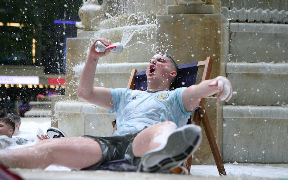 A Scotland fan enjoys a tinny in the Leicester Square fountain - PA