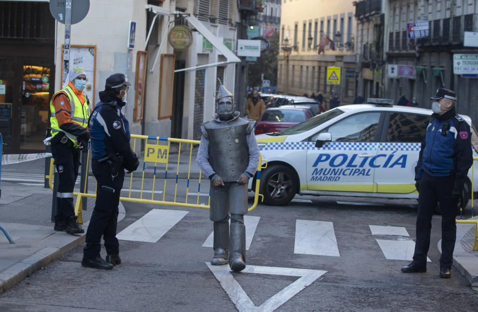A street performers passes police officers controlling the access to the Rastro flea market in Madrid, Spain, Sunday, Nov. 22, 2020. Madrid's ancient and emblematic Rastro flea market reopened Sunday after a contentious eight-month closure because of the COVID-19 pandemic that has walloped the Spanish capital. (AP Photo/Paul White)