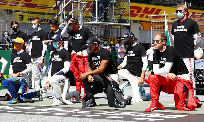 Formula One F1 - Austrian Grand Prix drivers, including Mercedes' Lewis Hamilton, Ferrari's Sebastian Vettel and others, kneel on the grid wearing anti-racism T-shirts before the race on July 5, 2020. / Credit: POOL / REUTERS