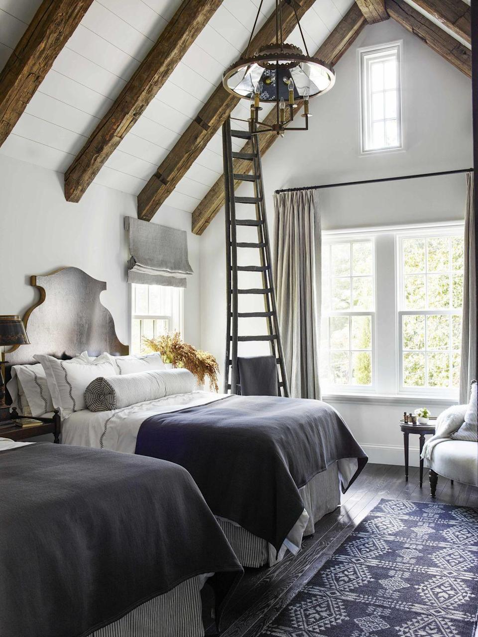 """<p>To honor the craftsmanship and original architecture of this <a href=""""https://www.veranda.com/decorating-ideas/a28577679/amy-morris-atlanta-house-tour/"""" rel=""""nofollow noopener"""" target=""""_blank"""" data-ylk=""""slk:100-year-old home in Atlanta"""" class=""""link rapid-noclick-resp"""">100-year-old home in Atlanta</a>, designer <a href=""""https://amymorrisinteriors.com/"""" rel=""""nofollow noopener"""" target=""""_blank"""" data-ylk=""""slk:Amy Morris"""" class=""""link rapid-noclick-resp"""">Amy Morris</a> kept the color palette simple. Creamy white walls and deep textiles such as the <a href=""""https://moattar.com/"""" rel=""""nofollow noopener"""" target=""""_blank"""" data-ylk=""""slk:Moattar"""" class=""""link rapid-noclick-resp"""">Moattar</a> rug allow the warm, rich ceiling beams and sculptural headboard (<a href=""""https://www.hollandmacrae.com/"""" rel=""""nofollow noopener"""" target=""""_blank"""" data-ylk=""""slk:Holland MacRae"""" class=""""link rapid-noclick-resp"""">Holland MacRae</a>) shine in this guest room. </p>"""