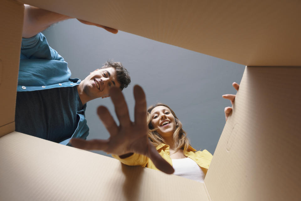 Happy couple opening a cardboard box and looking inside, they are smiling and cheerful
