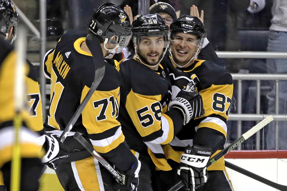Pittsburgh Penguins' Kris Letang (58) celebrates his goal with Evgeni Malkin (71) and Sidney Crosby (87) during the second period of the team's NHL hockey game against the Montreal Canadiens in Pittsburgh, Friday, Feb. 14, 2020. (AP Photo/Gene J. Puskar)