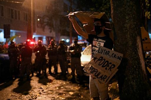 """A man demonstrates near military police during a """"Stop Bolsonaro"""" protest against political scandals engulfing the president and his family in late June 2020 in Rio de Janeiro"""
