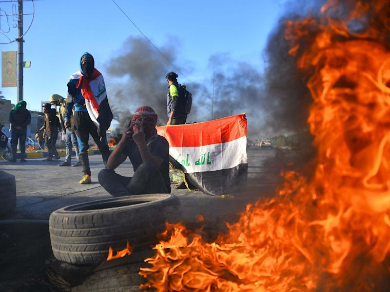 Iraqi demonstrators block a road with burning tyres in the central shrine city of Najaf, on 5 January 2020, to protest turning the country into an arena for US-Iran conflicts: AFP/Getty