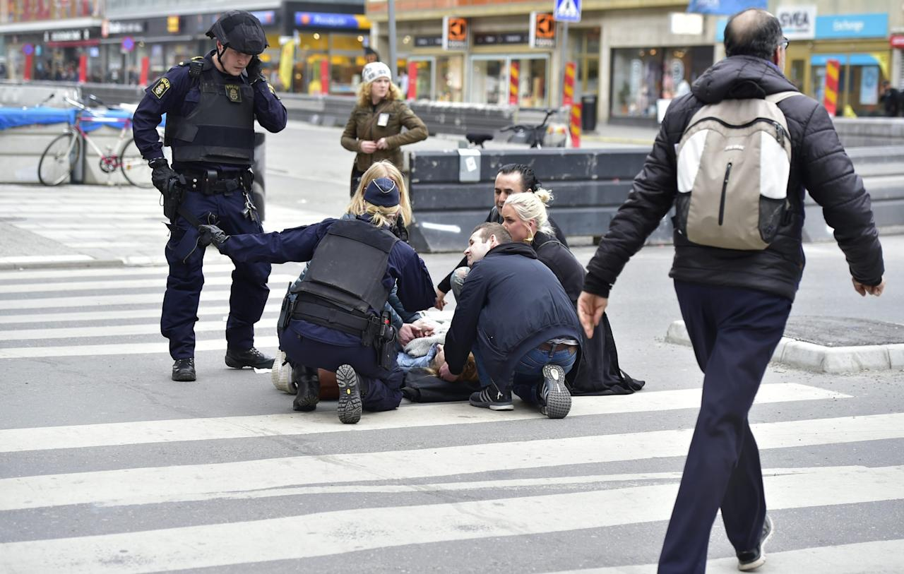 <p>Officers and passers-by tend to another of the injured (Rex) </p>