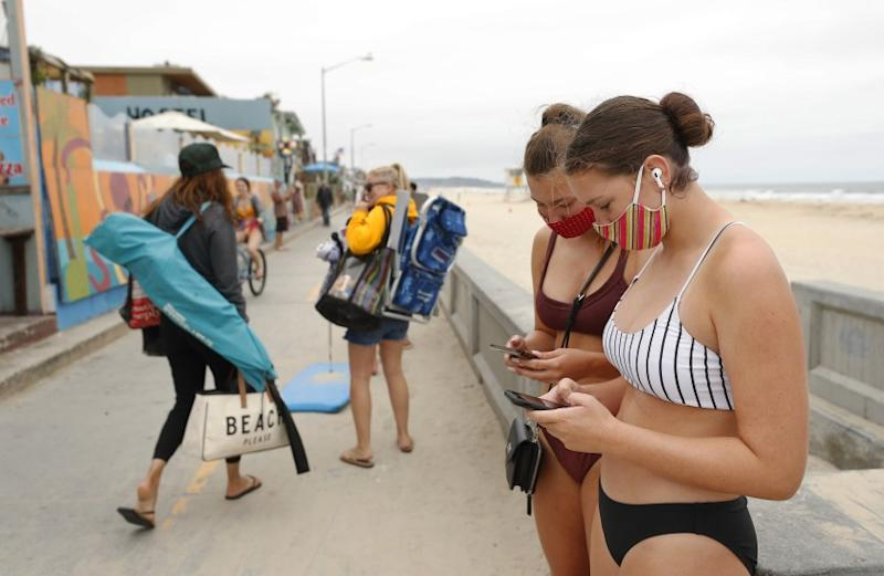 Coronavirus cases in California continued a troubling spike this week. Here, Calyssa Hill, left, and Hadley Hall, where masks while looking at their phones along the Pacific Beach boardwalk on June 24, 2020.