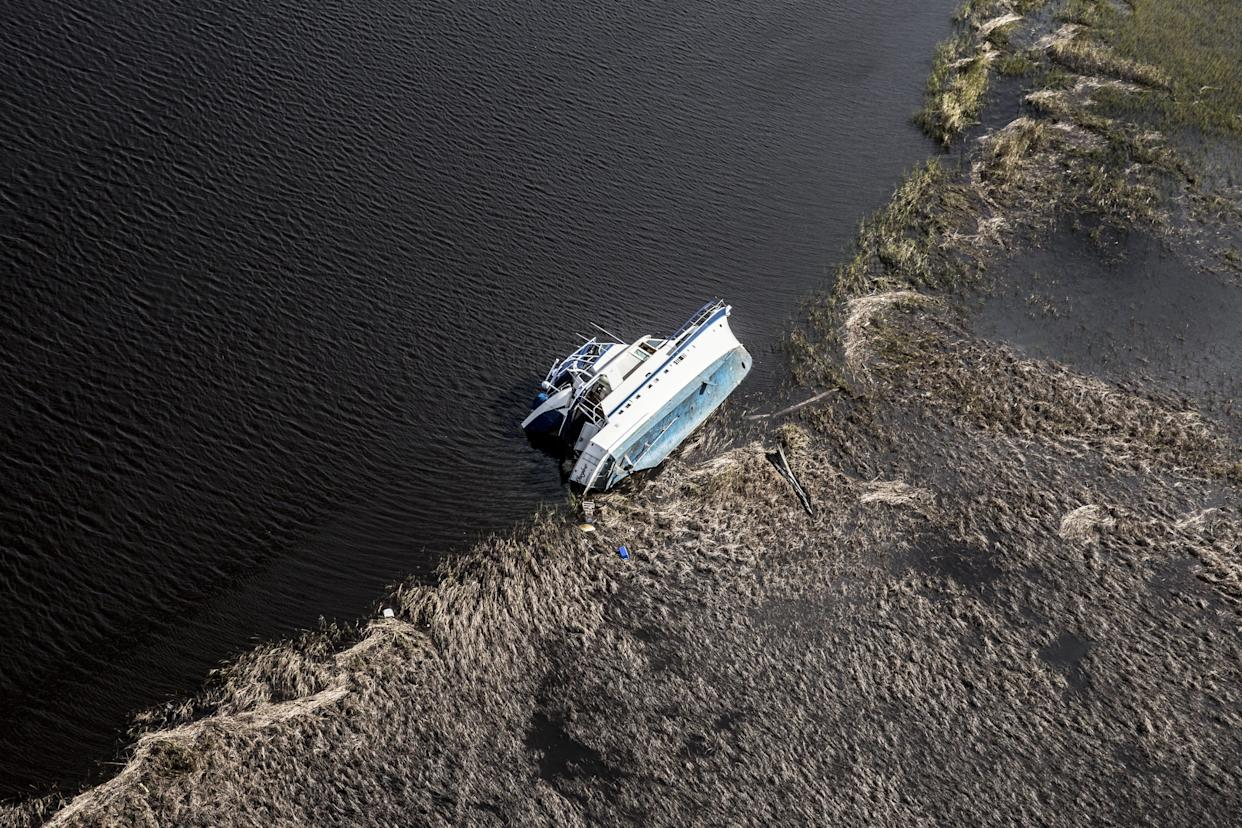 A boat lies capsized on the Cape Fear River in Wilmington.