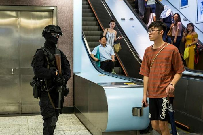 Bystanders look at a riot police officer (L) standing guard inside a train station in the Causeway Bay district of Hong Kong (AFP Photo/ISAAC LAWRENCE)