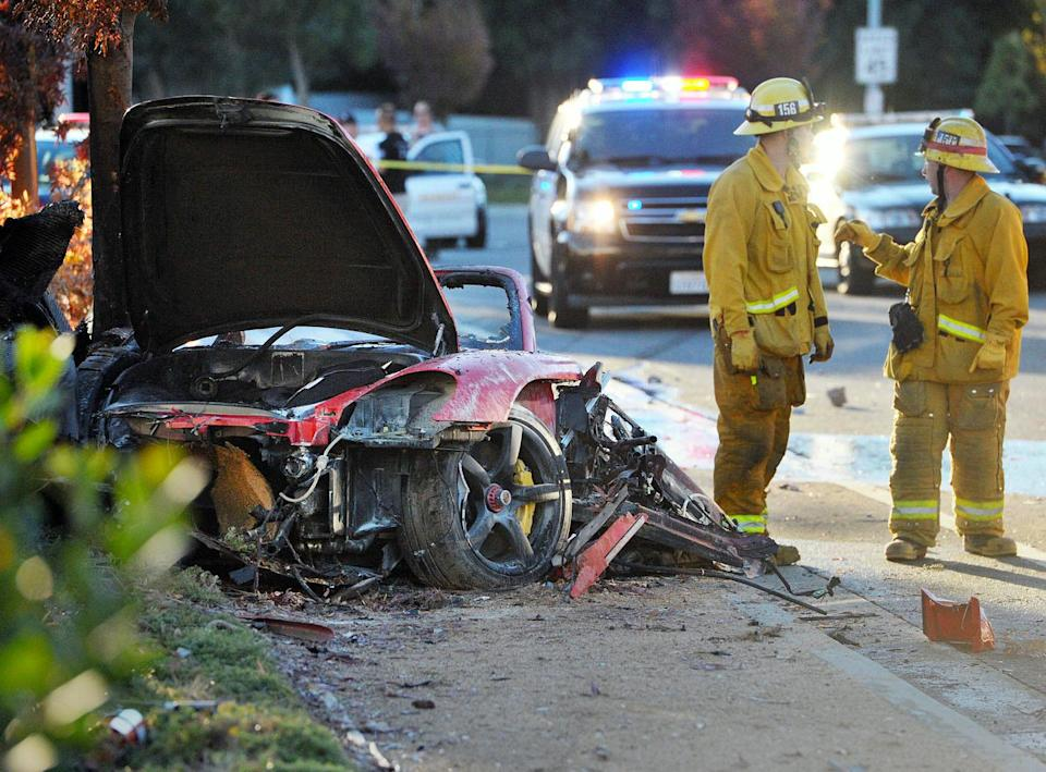 FILE - In this Saturday, Nov. 30, 2013, file photo, firefighters work next to the wreckage of a Porsche that crashed into a light pole killing actor Paul Walker and his Roger Rodas in Valencia, Calif. Crash investigators have determined that the Porsche was traveling approximately 90 mph when it lost control on a city street and smashed into a light pole, killing the actor and his friend. A person who has reviewed the investigators' report told The Associated Press that it concluded unsafe driving, not mechanical problems, caused the crash. The person requested anonymity because the report has not been officially released yet. (AP Photo/The Santa Clarita Valley Signal, Dan Watson) LOS ANGELES DAILY NEWS OUT. MANDATORY CREDIT