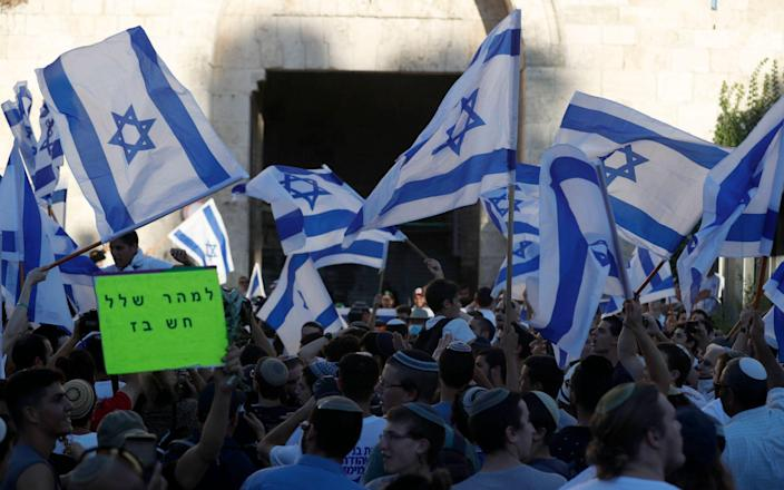Members of Israeli right-wing groups taking part in the 'Flag March' wave Israeli flags next to Damascus gate of Jerusalem's Old City, 15 June 2021. - Shutterstock