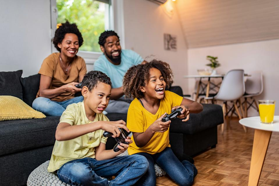 Happy African American family playing video games in the living room.
