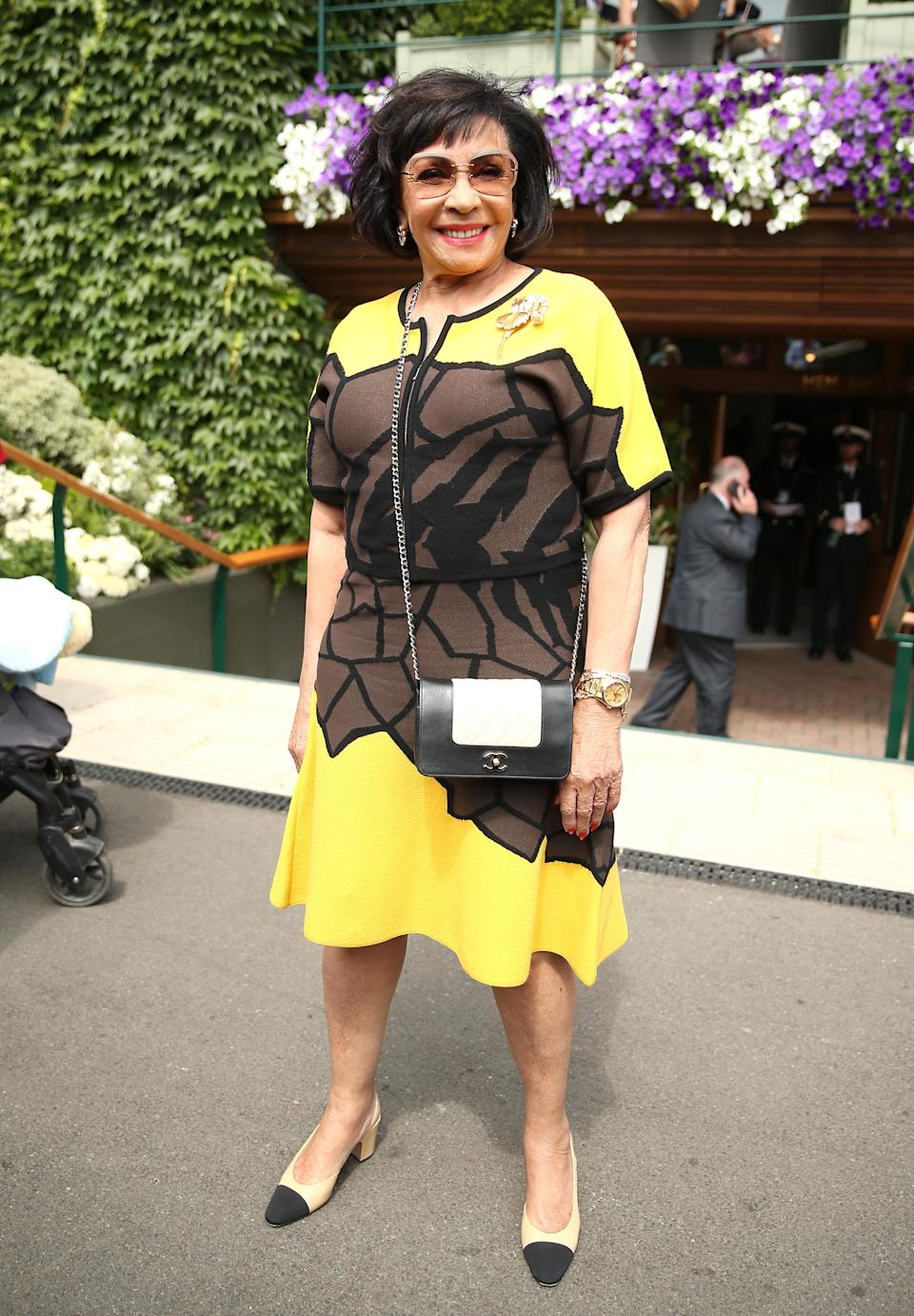 <p>Dame Shirley Bassey made her debut at Wimbledon 2018 in a sun-hued dress and monochrome cross-body bag. <em>[Photo: PA]</em> </p>