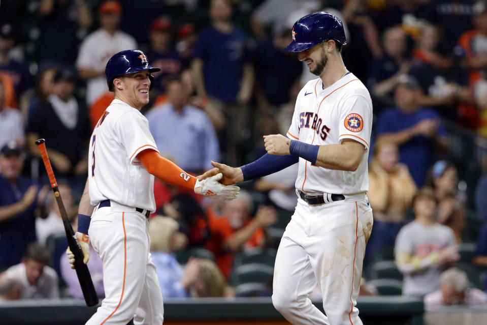 Houston Astros' fielder Myles Straw, left, and Kyle Tucker, right, celebrate Tucker's home run during the fifth inning of a baseball game against the Los Angeles Angels Tuesday, May 11, 2021, in Houston. (AP Photo/Michael Wyke)