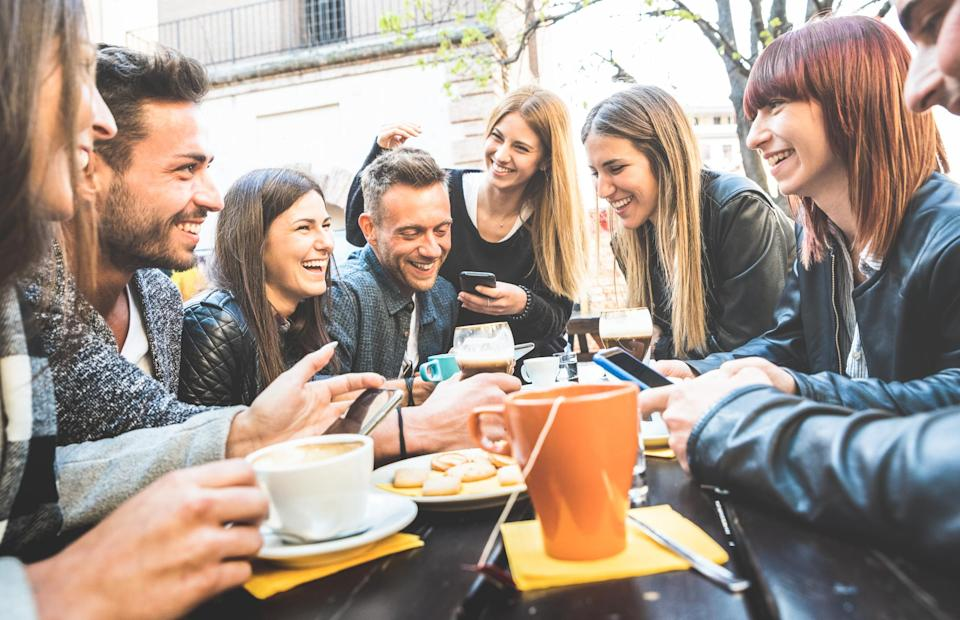 Men and women sharing drinks at a coffee bar while smiling, laughing, and looking at their smartphones