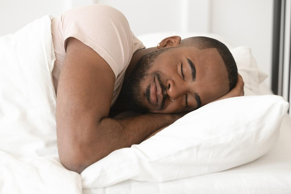 A young Black man sleeping comfortably in bed.