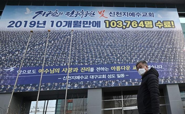 A man wearing a face mask walks in front of the Daegu branch of the Shincheonji Church of Jesus in the southeastern city of Daegu on Feb. 21, 2020 as more than 80 members of Shincheonji have now been infected with the COVID-19 coronavirus.