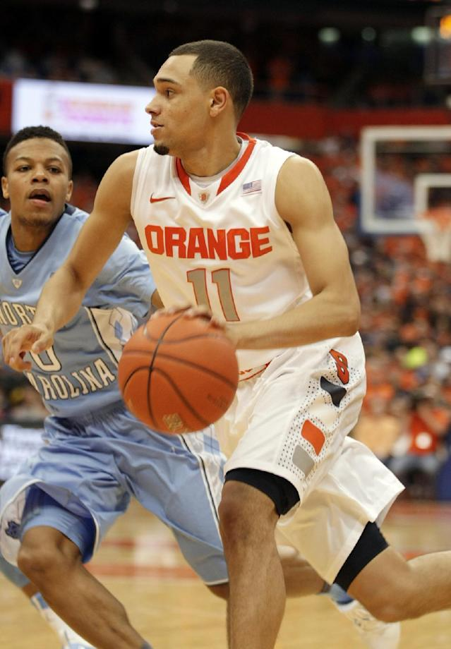 Syracuse's Tyler Ennis, right, drives to the basket against North Carolina's Nate Britt, left, in the second half of an NCAA college basketball game in Syracuse, N.Y., Saturday, Jan. 11, 2014. Syracuse won 57-45. (AP Photo/Nick Lisi)