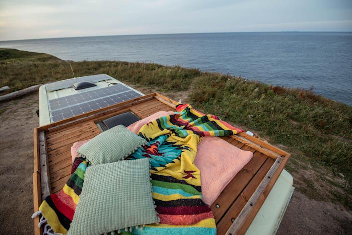 The roof top deck with blankets and pillows on it overlooks a body of water to the right