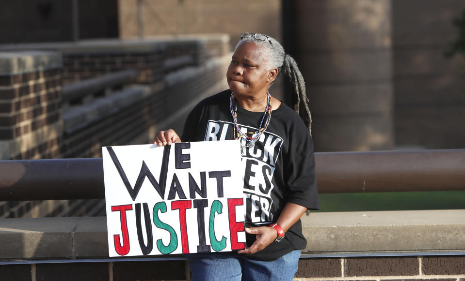 Alpha Thomas holds a sign outside the Frank Crowley Courthouse before the start of the murder trial of former Dallas police Officer Amber Guyger in downtown Dallas, Monday, Sept. 23, 2019. Guyger is on trial for shooting and killing her unarmed neighbor Botham Jean in the Dallas apartment building they both lived in. (AP Photo/LM Otero)