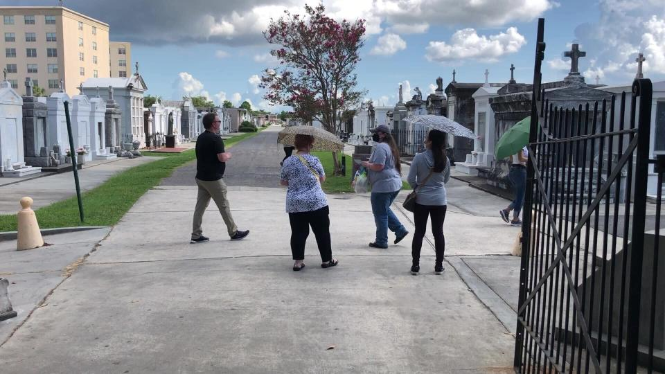 Tourists wander through a historic New Orleans cemetery on Thursday, Aug. 12, 2021. The city's vital tourism industry was devastated by the COVID-19 epidemic in 2020. It had begun making a comeback in recent months as vaccines have become available. But the spread of the highly contagious delta variant of the coronavirus and a low vaccination rate in Louisiana are being blamed for a resurgence of COVID-19 that has stressed hospitals and led to cancellations, for the second year, of tourist-drawing events. (AP Photo/Kevin McGill)