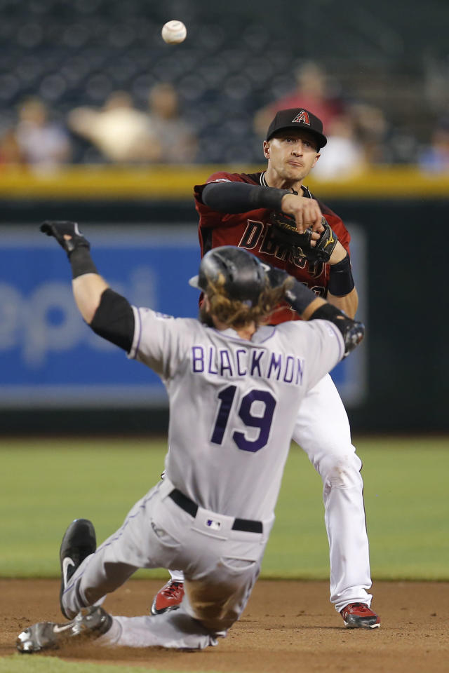 Arizona Diamondbacks shortstop Nick Ahmed turns the double play while avoiding Colorado Rockies' Charlie Blackmon (19) on a ball hit by Ryan McMahon in the seventh inning during a baseball game, Wednesday, Aug. 21, 2019, in Phoenix. (AP Photo/Rick Scuteri)