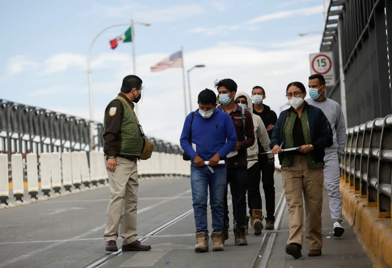 Migrants are escorted by agents from Mexico's National Migration Institute (INM) after being deported from the United States, in Ciudad Juarez