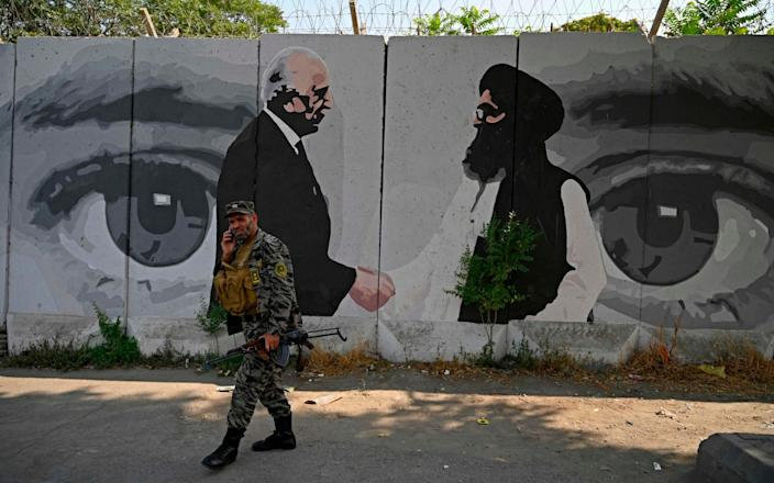 A security personnel walks past a wall mural with images of US Special Representative for Afghanistan Reconciliation Zalmay Khalilzad (L) and Taliban co-founder Mullah Abdul Ghani Baradar, in Kabul - AFP/AFP