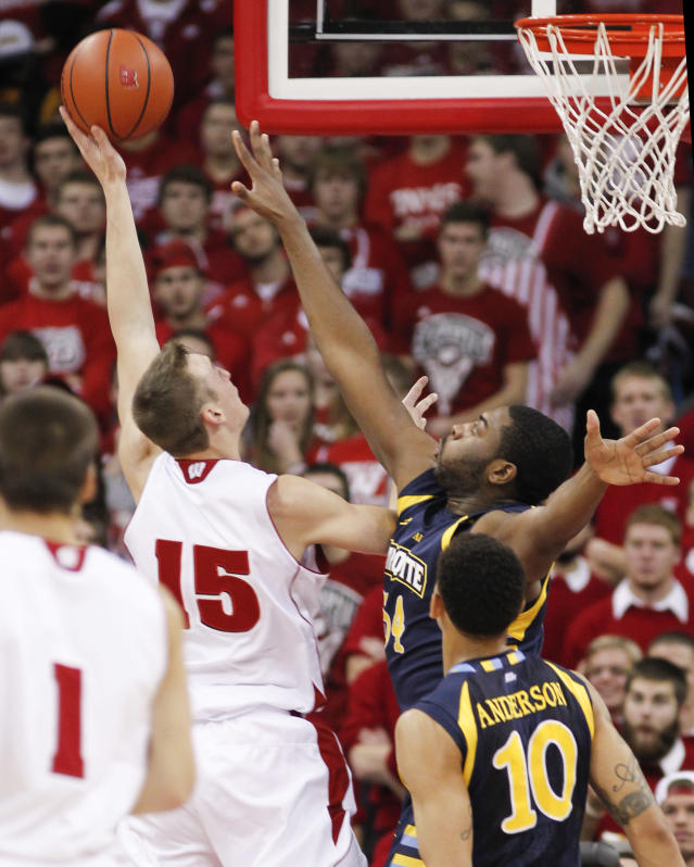 Wisconsin's Sam Dekker (15) shoot over Marquette's Davante Gartner during the first half of an NCAA college basketball game Saturday, Dec. 7, 2013, in Madison, Wis. (AP Photo/Andy Manis)