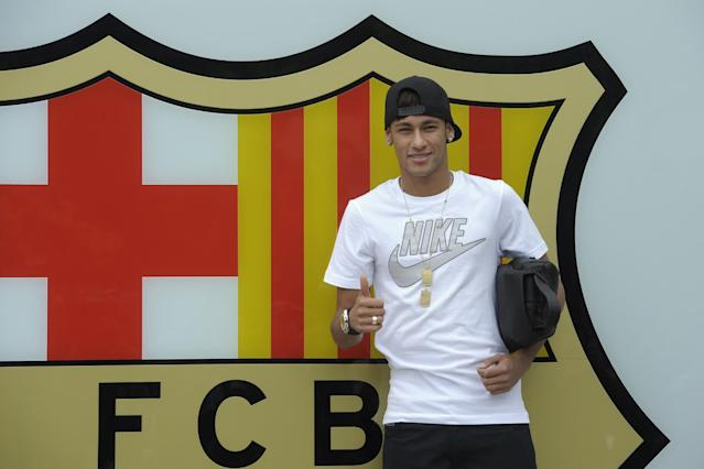 """FILE - In this June 3, 2013 file photo, FC Barcelona's then new signing Neymar gestures upon his arrival at the club's office at the Camp Nou stadium in Barcelona, Spain. A Spanish court has charged Spanish league champion Barcelona with tax fraud of euro 9.1 million ($12.5 million) over the transfer of Brazil forward Neymar. Judge Pablo Ruz said in his decision, released on Thursday, Feb. 20, 2014 there was enough evidence to merit charges over Neymar's 57 million-euro (then $77 million) move from Santos last summer. Thursday's decision comes a day after public prosecutor Jose Perals charged Barcelona with fabricating simulated contracts and using """"financial engineering"""" to defraud the Spanish Treasury. Barcelona has denied the charges. (AP Photo/Manu Fernandez, File)"""