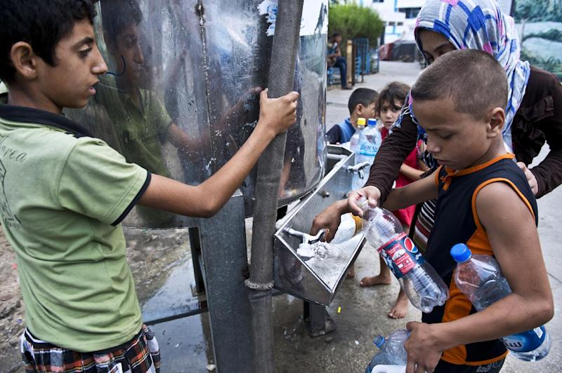 Palestinian children who sought refuge at a UN school fill out plastic bottles with fresh water after the tanks were replenished on August 15, 2014, in Gaza City (AFP Photo/Roberto Schmidt)