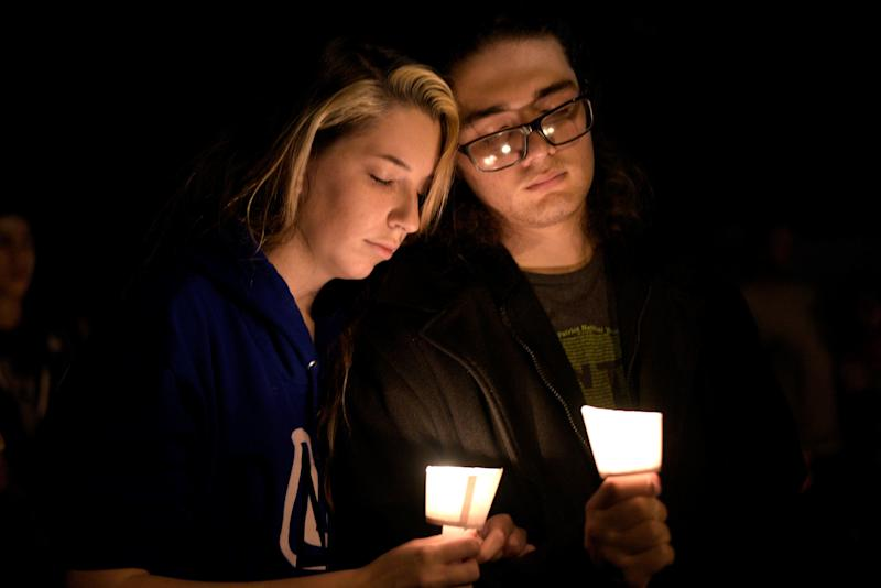 Bailey Lejeaune and David Betancourt attend a candlelight vigil after a mass shooting at the First Baptist Church.