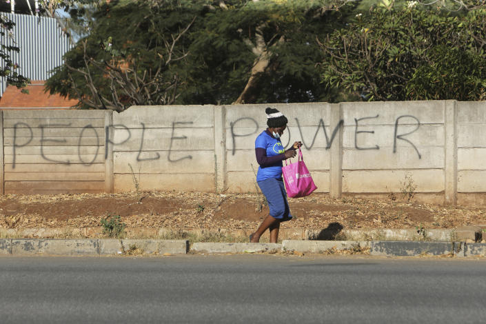 "A woman walks past a wall with graffiti advocating for the empowerment of people in the streets of Harare, in this Tuesday, June, 9, 2020 photo. Unable to protest on the streets, some in Zimbabwe are calling themselves ""keyboard warriors"" as they take to graffiti and social media to pressure a government that promised reform but is now accused of gross human rights abuses.(AP Photo/Tsvangirayi Mukwazhi)"