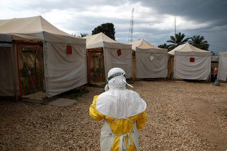 FILE PHOTO: A health worker wearing Ebola protection gear, walks before entering the Biosecure Emergency Care Unit (CUBE) at the ALIMA (The Alliance for International Medical Action) Ebola treatment centre in Beni, in the Democratic Republic of Congo, March 30, 2019. Picture taken March 30, 2019.REUTERS/Baz Ratner/File Photo