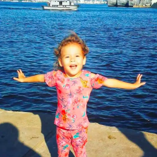 Rebecca Rayane da Silva Pereira stands with her arms wide in front of the ocean.
