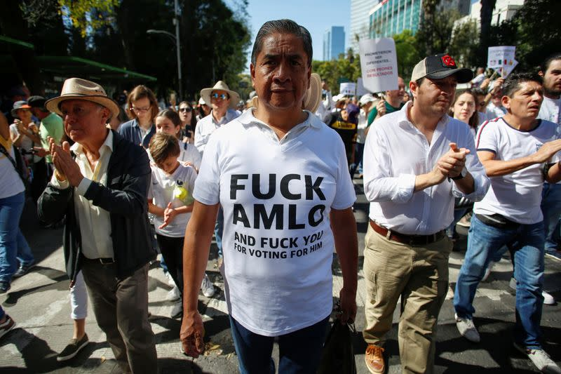 Demonstrators are seen during a march to protest against violence on the first anniversary of President Andres Manuel Lopez Obrador taking office, in Mexico City
