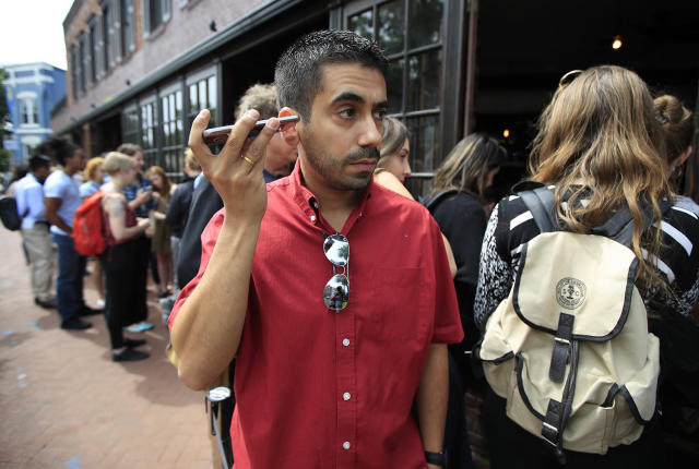 <p>Orlando Lopez of Reston, Va., listens to live broadcast broadcast of former FBI director James Comey testifying before the Senate Select Committee on Intelligence, on Capitol Hill, with a group of other people lined up at Shaw's Tavern in Washington, June 8, 2017. (Manuel Balce Ceneta/AP) </p>