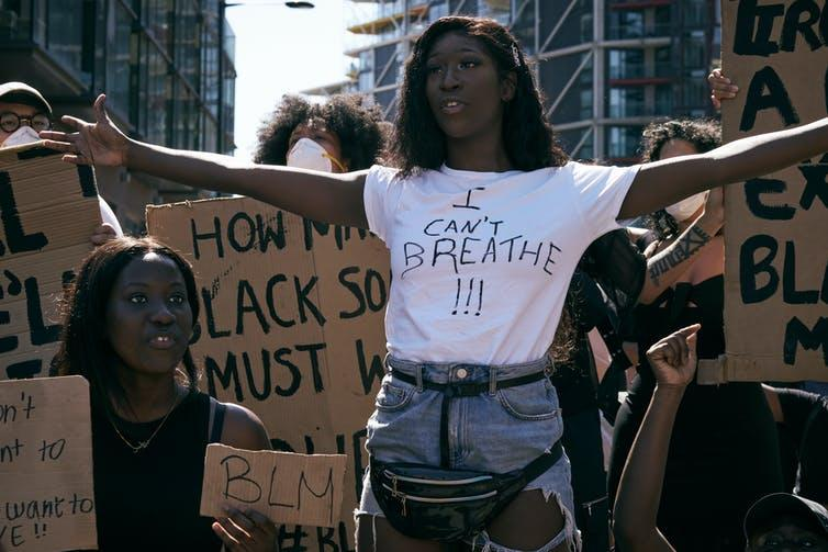 Black Lives Matters protesters holding signs and marching.