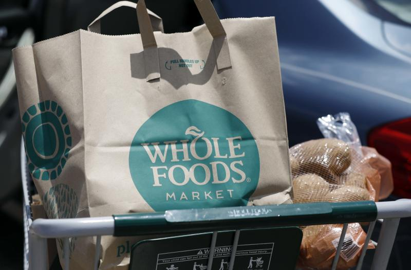 FILE - In this Friday, June 16, 2017, file photo, groceries from Whole Foods Market sit in a cart before being loaded into a car outside a store in Jackson, Miss. Ahead of Thanksgiving 2017, Amazon is giving Prime members their first taste of special discounts at its recently-acquired Whole Foods stores. (AP Photo/Rogelio V. Solis, File)